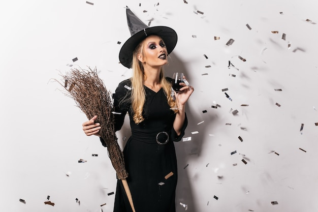 Blithesome young witch drinking wine. carefree woman in halloween attire posing at party.