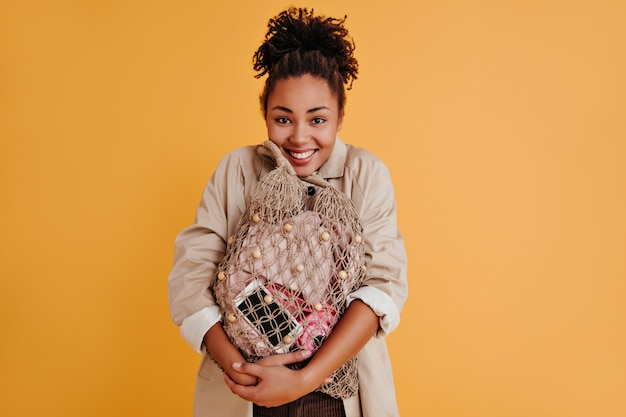ストリングバッグを持って笑っている明るい若い女性
