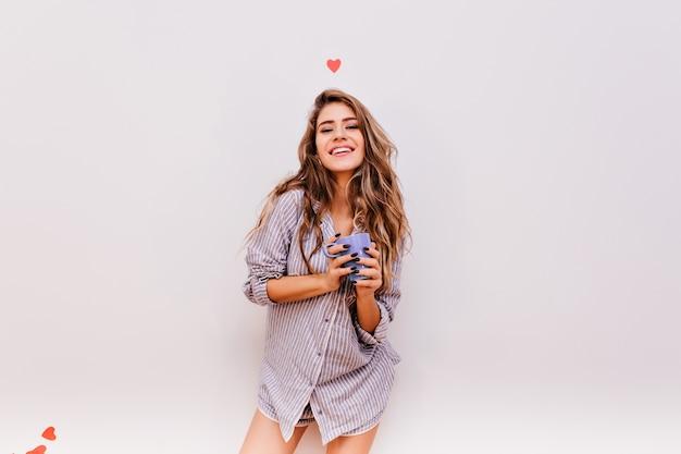 Веселая молодая женщина в полосатой рубашке смеется утром