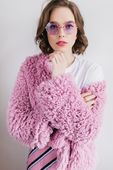 Blithesome young woman in trendy round glasses standing on white wall. jocund short-haired female model in fur coat.