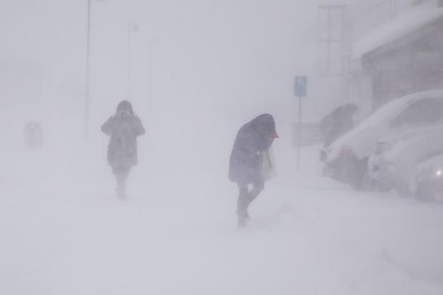 Метель в лонгйире. люди в снегопаде. абстрактный размытый зимний погодный фон