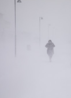Blizzard in longyearbyen, woman walking in snowfall. abstract blurry winter weather background