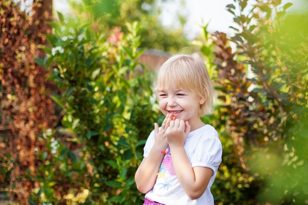 緑豊かな公園で屋外の小学校時代の幸せな小さなblobde女の子のクローズアップの肖像画