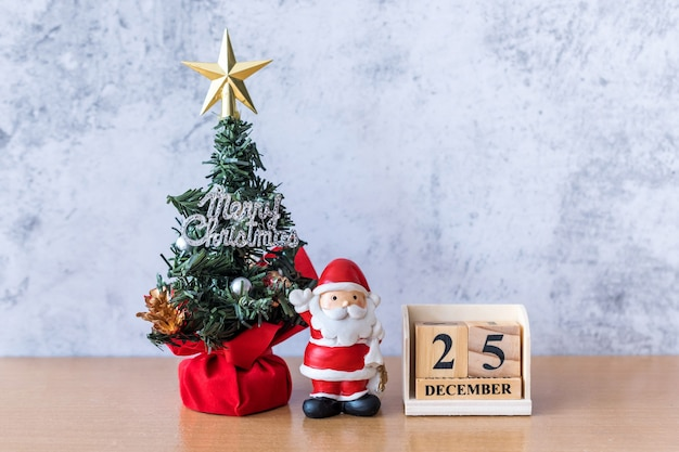 Block calendar date december 25 calendar and christmas decoration - santa clause, tree and gift on wooden table. christmas and happy new year concept