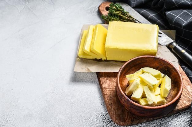신선한 버터, 낙농 제품 블록. 회색 배경입니다. 상위 뷰입니다. 공간을 복사하십시오.