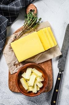 회색 테이블에 신선한 버터의 블록입니다.