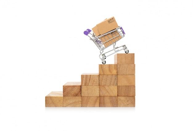 木製block.onlineショッピングの概念成長成功プロセス上のトロリーの紙箱