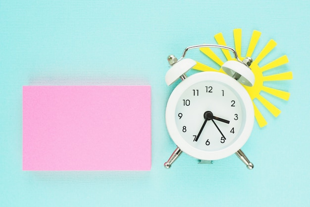 A block of pink stickers, a white alarm clock and a yellow paper sun peeking from behind it on a blue paper background.