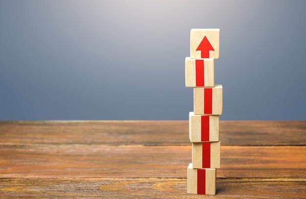 赤い矢印の付いたブロックタワー成長の発展と進歩の概念キャリアアップのステップバイステップ