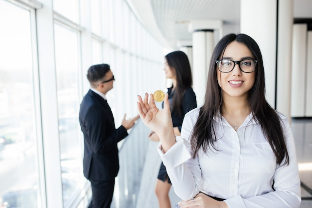 Блокчейн и инвестиционная концепция. лидер бизнес-леди, держащий биткойн перед командой обсуждения в офисе.