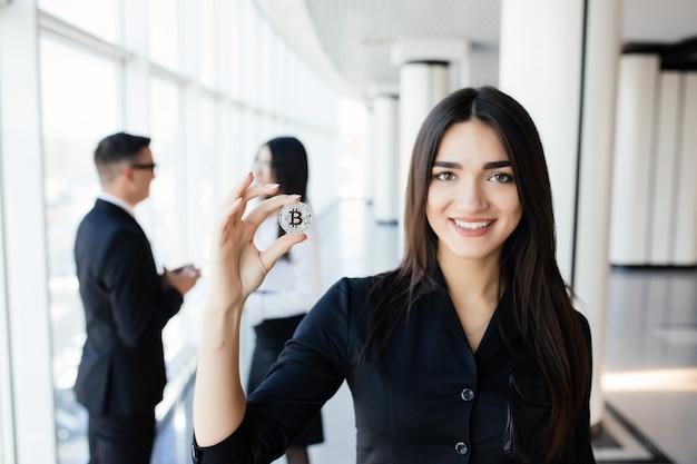 Блокчейн и инвестиционная концепция. лидер бизнес-леди, держащий биткойн перед своей командой обсуждения в офисе.