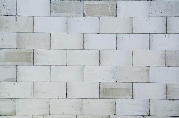 Блоки для стен здания, пеноблок. строительство и ремонт домов. белый пористый материал с узором для фона.