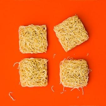 Blocks of instant noodles arranged over bright orange surface