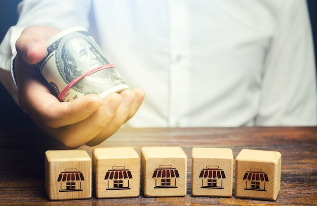 Blocks symbolizing business network and businessman holds out money. offer for purchase