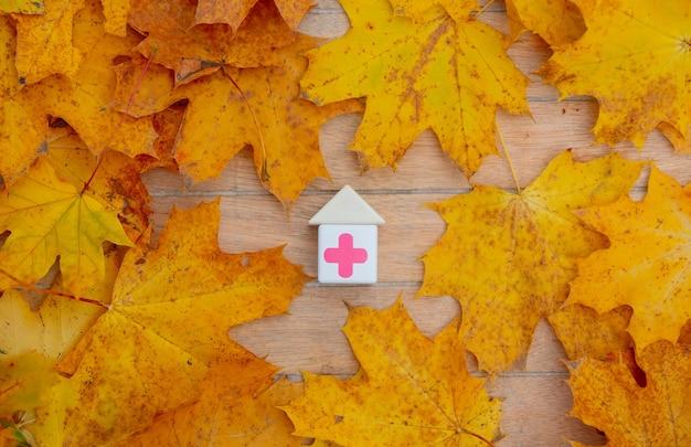 木製のテーブルの葉の横に医療の赤い十字が付いているブロック