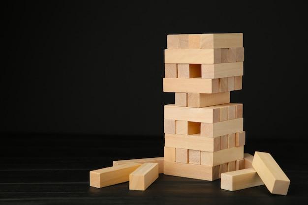 Blocks of wood on black background. tower