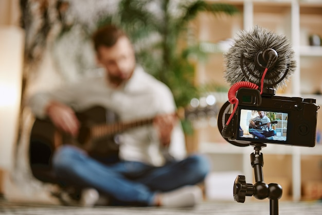 Блог о музыке крупным планом экрана цифровой камеры с мужским музыкальным блоггером, играющим