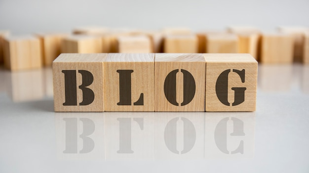 Слово блог состоит из деревянных блоков, лежащих на сером столе, концепция