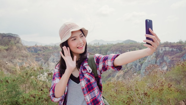 Blogger asian backpacker woman record vlog video on top of mountain, young female happy using mobile phone make vlog video enjoy holidays on hiking adventure.