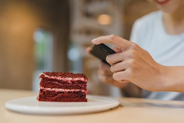 ブロガーアジア人フレンドリーな女性インフルエンサーがナイトカフェでケーキを食べる