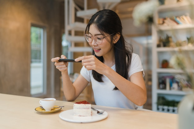Blogger asian friendly women influencer eat cake at night cafe