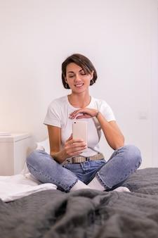 캐주얼 한 옷을 입은 집에서 블로거 아늑한 침실은 거울에 휴대 전화로 사진 셀카를 찍습니다.