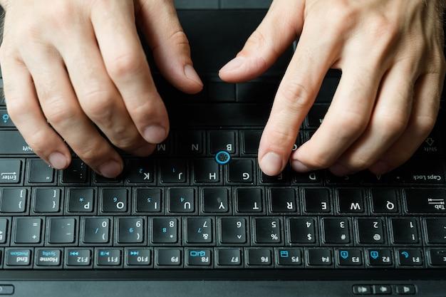 ブロガーのブログとソーシャルメディアのコンセプト。新しい投稿を書くノートパソコンのキーボードで入力する男の手。