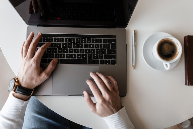 밝은 사무실에서 현대 노트북에서 작동하는 t- 셔츠에 블로거 사업가 남자. 노트북과 커피 한잔과 흰색 나무 바탕 화면에 상위 뷰