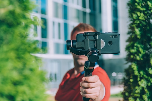Blogger in the city shoots video on a smartphone with a manual camera stabilizer.