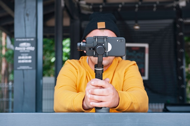 Blogger in coffee shoots video on a smartphone with a manual camera stabilizer.