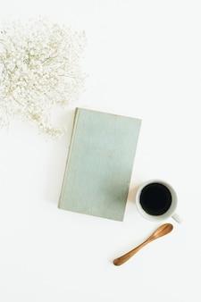 Стол блоггера с кофе, книгой, цветами на белой поверхности
