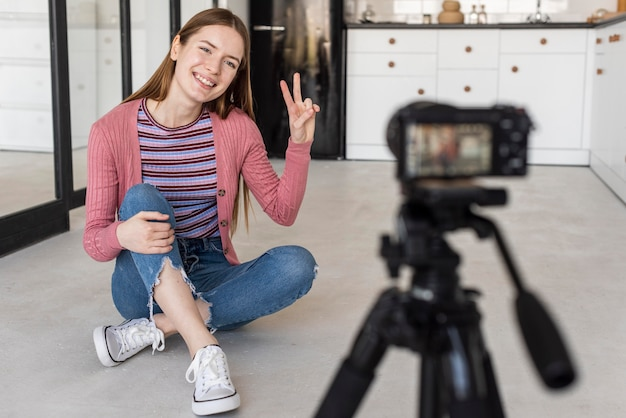 Blogger doing peace sign in front of camera