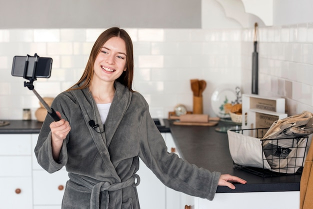 Blogger in dressing gown and recording herself at the kitchen