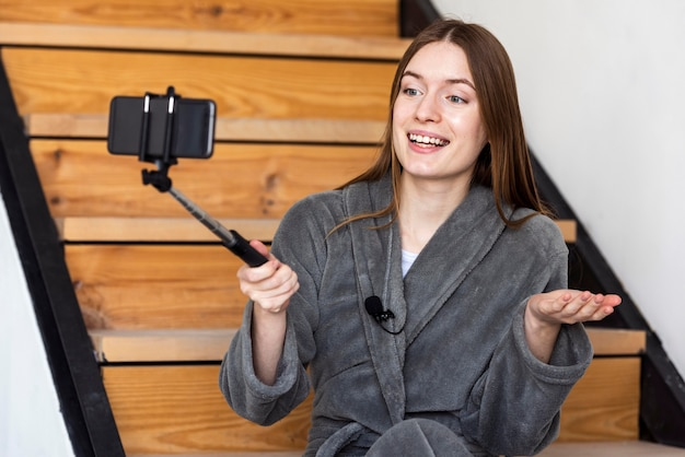 Blogger indressing gown and recording with smartphone
