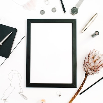 Blogger or freelancer workspace with blank screen photo frame protea flower notebook watches and feminine accessories on white background flat lay top view home office desk