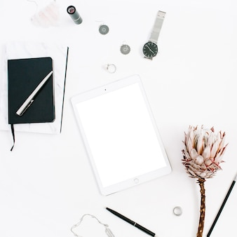 Blogger or freelancer workspace with blank screen tablet, protea flower, notebook, watches and feminine accessories on white background. flat lay, top view minimalistic decorated home office desk.