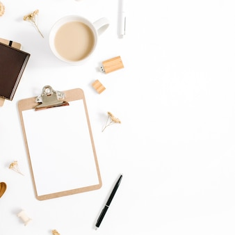 Blogger or freelancer workspace with clipboard, coffee mug, notebook and accessories on white background. flat lay, top view minimalistic brown styled home office desk. beauty blog concept.