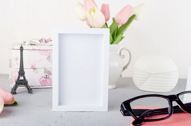 Blogger or freelancer workspace with tulips, notebook, clock and empty white frame for text.