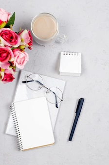 Blogger or freelancer workspace with tulips, notebook, clock and empty