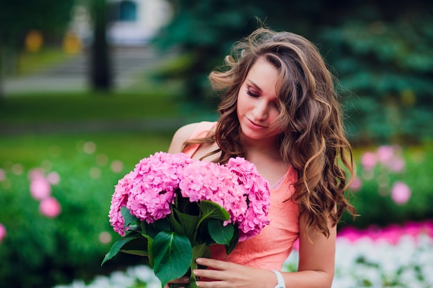 꽃 시장에서 꽃 다발을 들고 블로거 소녀. 블로깅 개념.