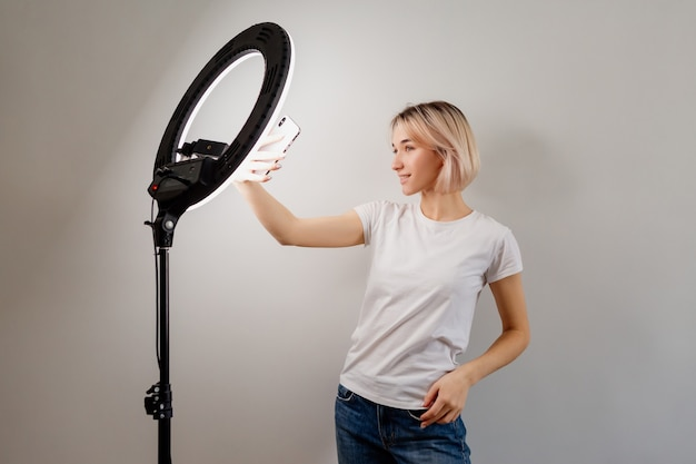 Blogger girl is broadcasting live via a smartphone under a ring lamp