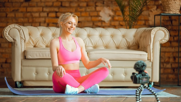 온라인 운동을하는 카메라가있는 스포츠 복장의 요가 매트에 앉아 블로거 소녀, 집에서 온라인 에어로빅 튜토리얼 기록