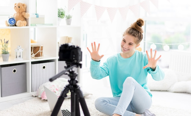 Blogger girl shooting vlog on camera in light room