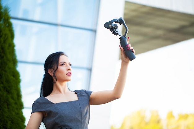 Blogger girl shoots a video about traveling on an electronic stabilizer.