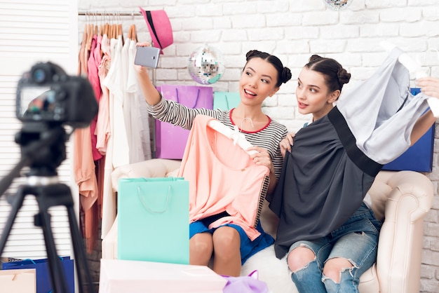 Blogger girls pull colorful dress from bags.