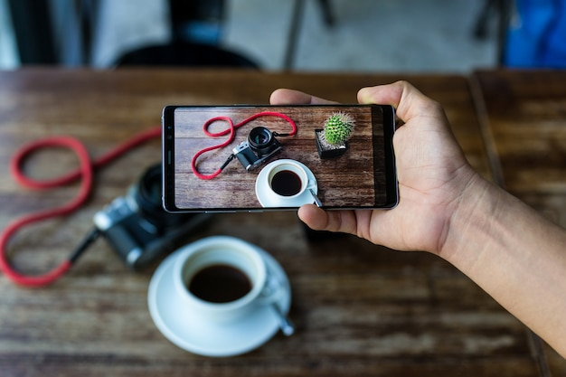 Blogger hand holding smart phone taking photo of coffee and camera on table.