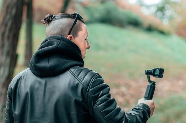 Блогер в черной одежде и солнцезащитных очках снимает видео с помощью экшн-камеры со стабилизатором камеры на подвесе в осеннем парке