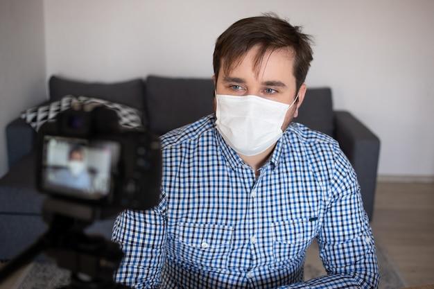 コロナウイルスの検疫に家にいる間、新しいvlogを記録しているマスクのブロガー