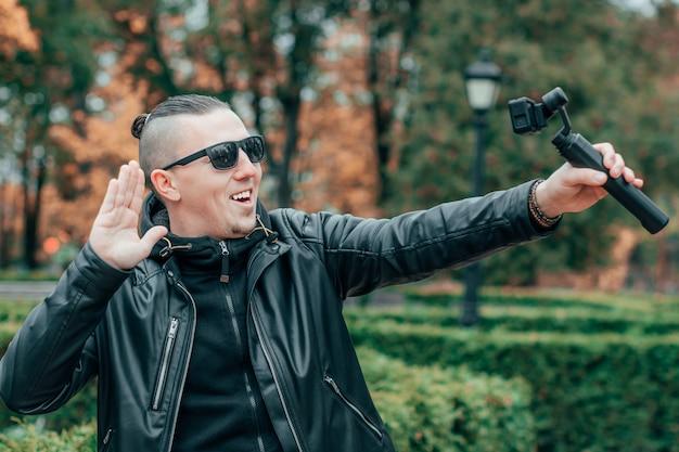 Блогер в солнцезащитных очках делает селфи или транслирует потоковое видео в осеннем парке с помощью экшн-камеры со стабилизатором камеры на подвесе.