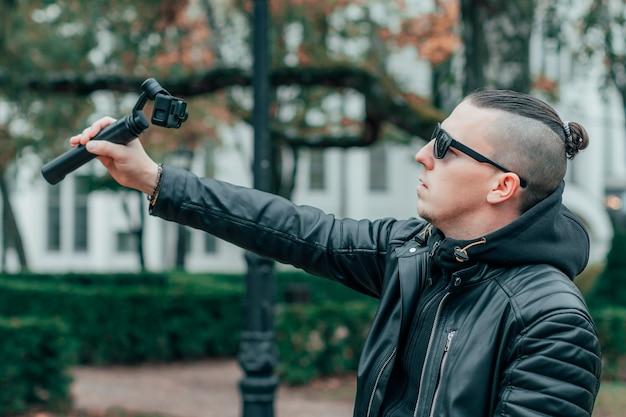ジンバルカメラスタビライザー付きのアクションカメラを使用して、秋の公園で自分撮りやストリーミングビデオを作成するサングラスのブロガー。